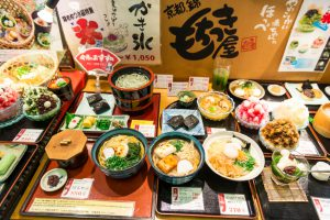Kyoto, Japan - August 12, 2014: Varieti of prepared Japanese food served in different bowls and plates with insriptions with price and ingredients. The food is exposed in front of a restaurant and look very colorful. Top view.